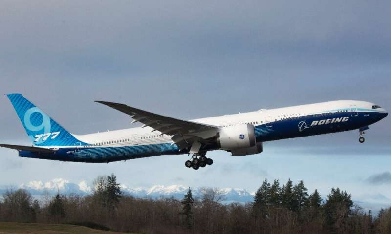 The snow-covered Olympic Mountains are pictured in the background as a Boeing 777X airplane takes off on its inaugural flight at