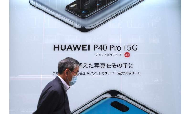 This picture taken on June 27, 2020 shows a man in Tokyo passing an advertisement for Huawei's 5G-capable smartphone; Apple is e