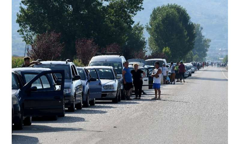 Thousands of Albanians queued in their cars at the Greek border, hoping to squeeze across and return to work before tougher entr