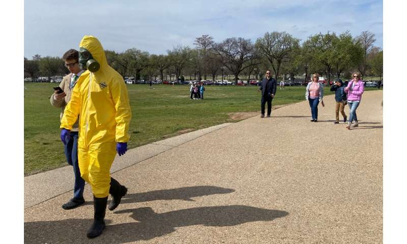 """Tourists walk around the Washington monument despite recommendations for """"social distancing"""" to protect against the co"""