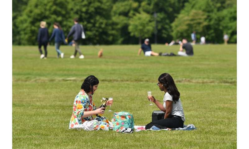Two women enjoy a drink in the grass in London's Hyde Park, after the were reopened for the first time in months