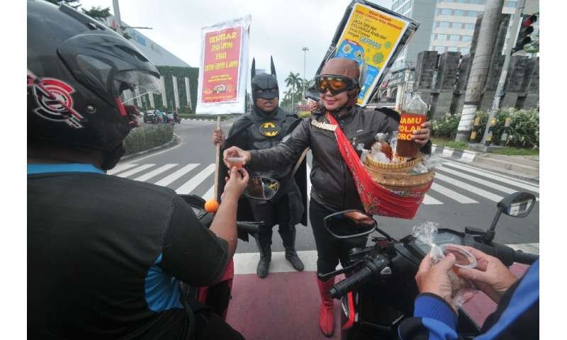 Vendors in fancy dress offer samples of a local herbal tonic to motorists in Solo, Indonesia