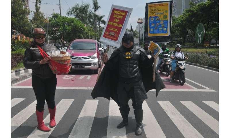 "Vendors wearing outfits of local superhero Gundala and Batman hawk traditional Indonesian herbal drinks known as ""jamu&quot"