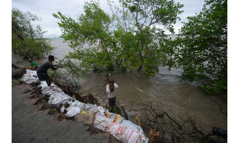 Villagers reinforce an embankment with sacks of soil ahead of the expected landfall of Cyclone Amphan, in Dacope, Bangladesh on