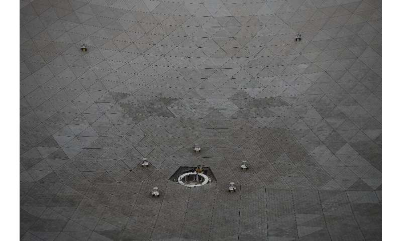 Workers are seen at the Five-hundred-meter Aperture Spherical radio Telescope (FAST) during maintenance work