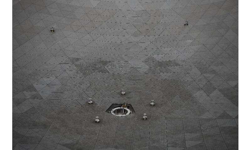 Los trabajadores miran un radiotelescopio esférico de quinientos metros de apertura (rápido) durante los trabajos de mantenimiento