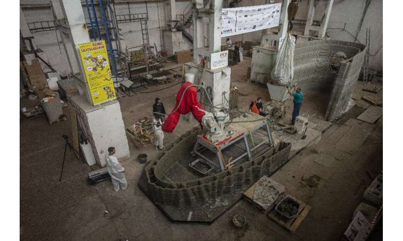 Workers check over the 3D construction, which is being printed from special concrete and is due to float down the river Vltava i