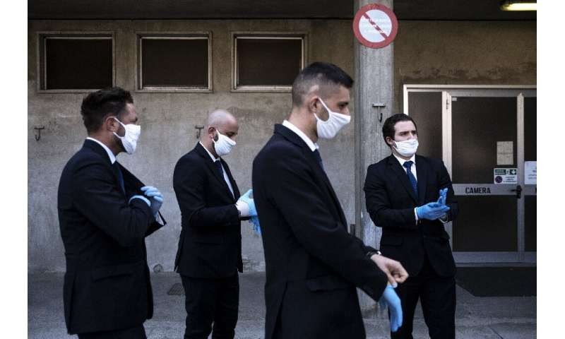 Workers from a funeral home company near Cuneo in northwestern Italy prepare to hold a service for a coronavirus victim