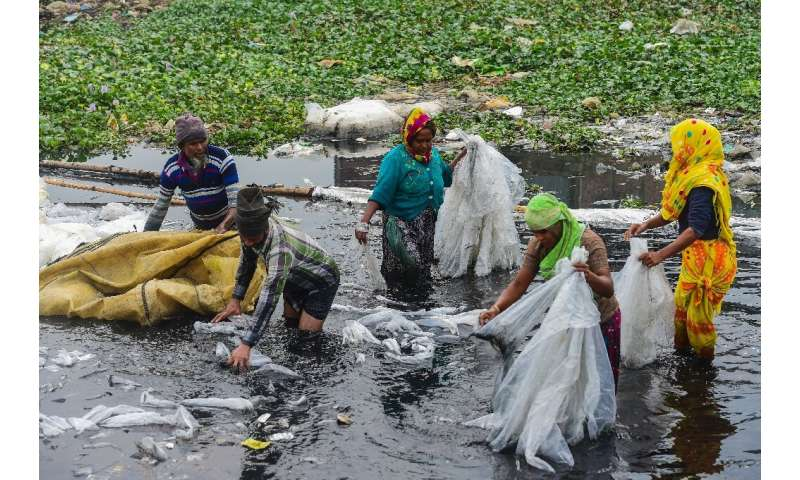 Workers scrub plastic bags used to carry industrial chemicals in the Buriganga river, which has become one of the world's most p