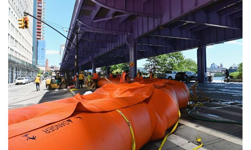 Workers set up temporary plastic flood barriers and sandbags known as 'Tiger Dams' in lower Manhattan to protect the area from f