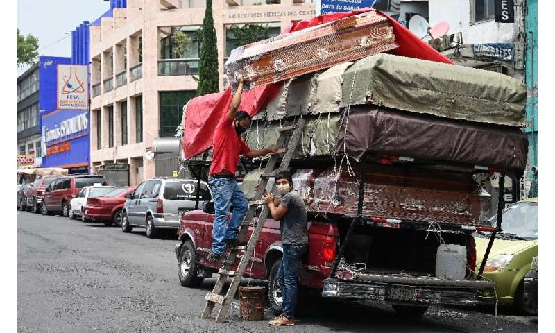 Workers unload coffins from a truck outside a funeral home located in front of the General Hospital in Mexico City