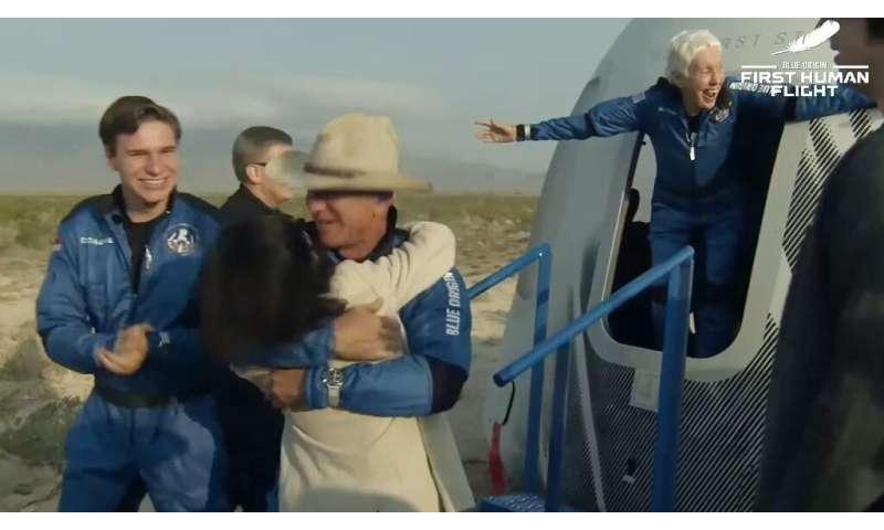 A joyful Wally Funk (R) emerges from the Blue Origin capsule