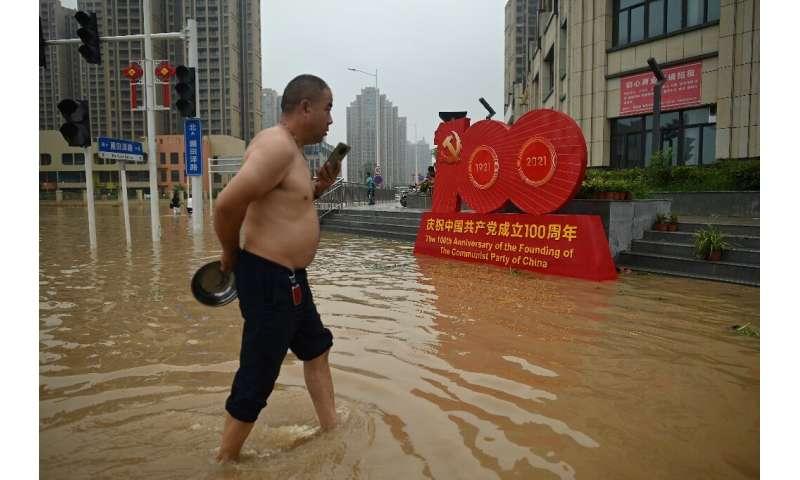 A man wades through a flooded street in  Zhengzhou