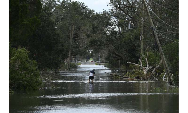A person wades through flood waters in Norco, Louisiana, on August 30, 2021