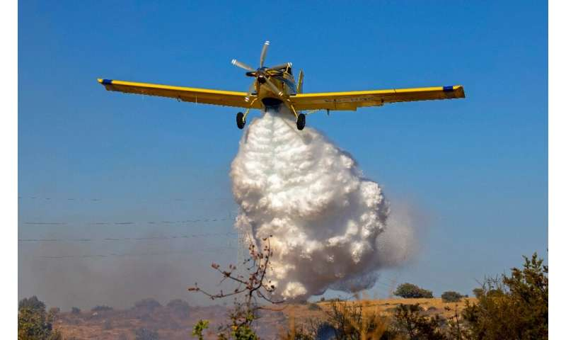 A Spanish Air Tractor firefighting plane dumps water on the southern slopes of the Troodos mountains close to Agioi Vavatsinias