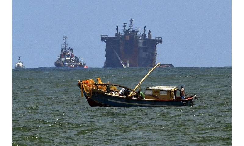 A Sri Lankan fishing boat operates against the backdrop of the MV X-Press Pearl, which lies partially submerged in shallow seas