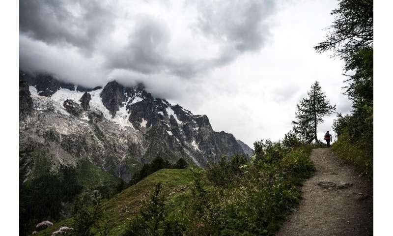 An hiker walks on a path near the Planpicieux (L) and Grand Jorasses Glaciers (2L) in Courmayeur