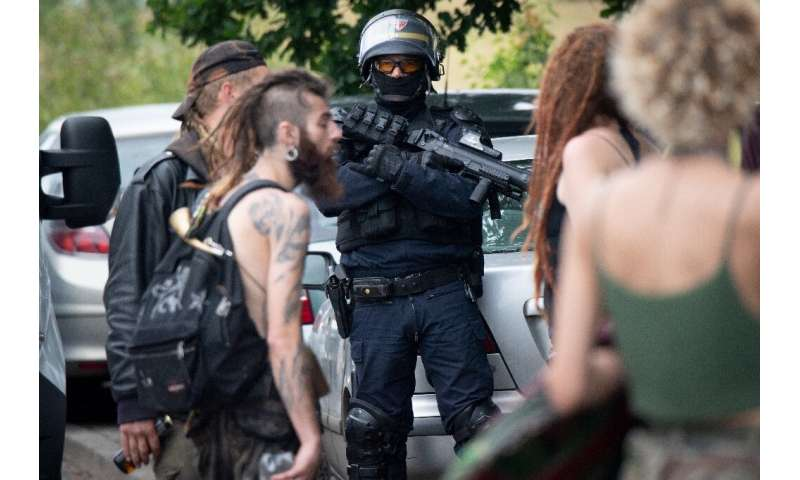 An officer looks on as police evacuate partygoers after an illegal rave in a field in Redon, France