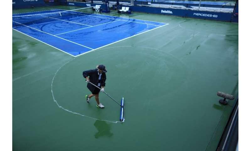 El personal de la cancha limpia la lluvia de las canchas en el Centro Nacional de Tenis Billie Jean King de la USTA en Nueva York, el 1 de septiembre de 2021