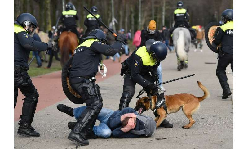 Dutch anti-riot police officers react during a demonstration against the government and anti-covid measures at the Malieveld in