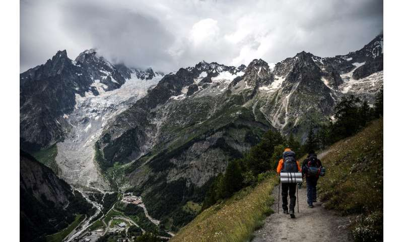 Hikers walk near the Brenva Glacier in Courmayeur, north-western Italy