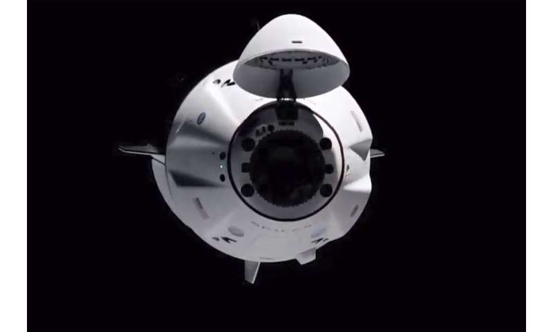 Old SpaceX capsule delivers new crew to space station