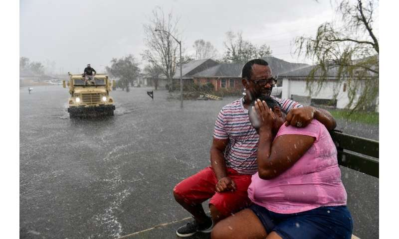People ride out of a flooded neighborhood in LaPlace, Louisiana on August 30, 2021