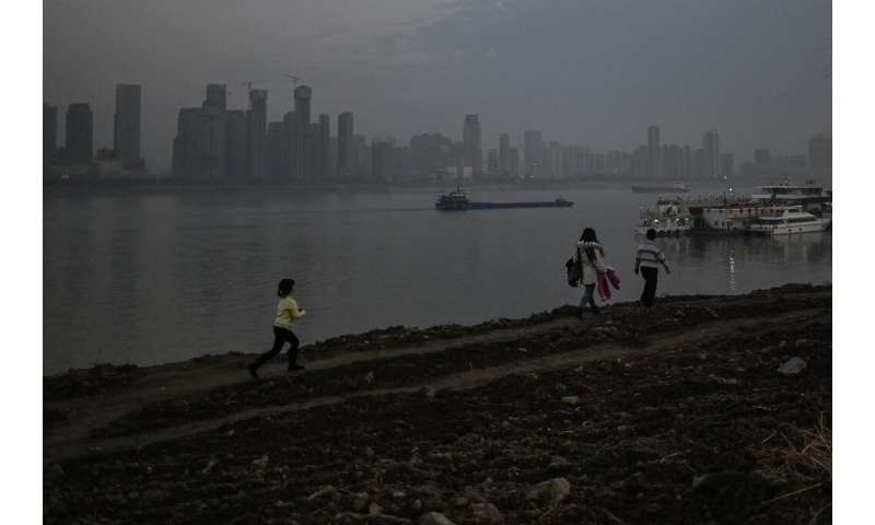 People walk in a park next to the Yangtze river in Wuhan on Wednesday
