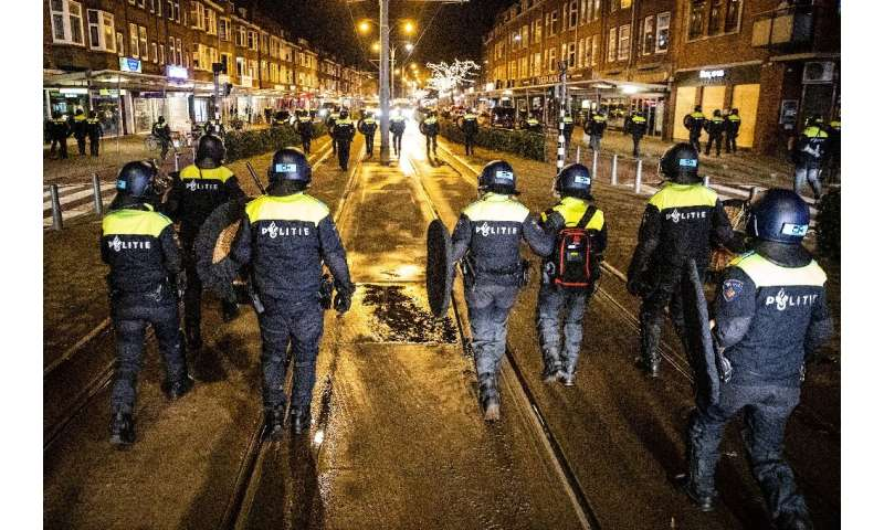 Police officers patrol the streets of Rotterdam a day after clashes with demonstrators protesting against new Covid-19 restricti