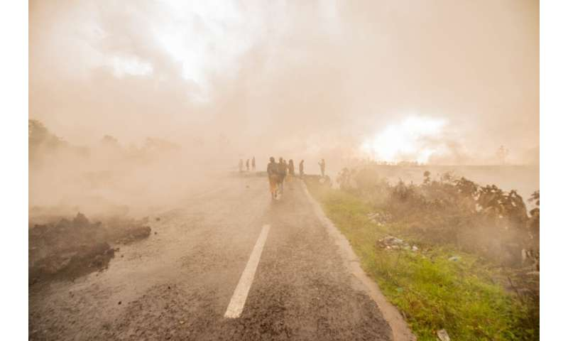 Residents on Sunday walked through the smoke from the smouldering lava