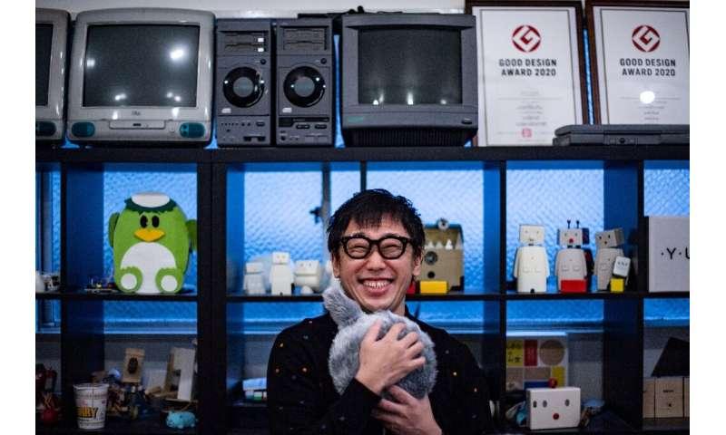 Shunsuke Aoki, CEO Yukai Engineering, memeluk bantal robotik Qoobo, yang memiliki ekor mekanis yang bergoyang.