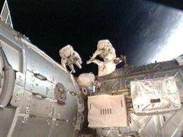 Astronauts work outside the International Space Station