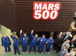Members of the Mars 500 crew wave before being locked into the isolation facility in Moscow