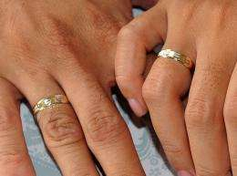 A couple holds hands showing their wedding rings