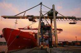 A crane loads containers on a cargo ship