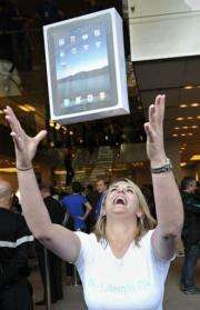 A customer celebrates after buying an iPad at a London store