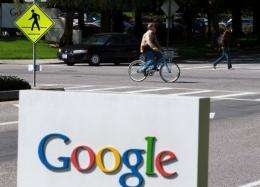 A cyclist rides by a sign outside of the Google headquarters in Mountain View, California