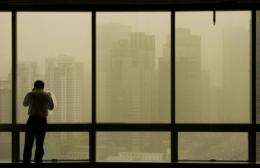 A man stands by windows as a sandstorm hits Beijing
