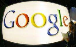 A visitor walks past the logo of Internet search engine giant Google