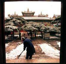 A woman sweeps snow off the steps of a temple in Beijing