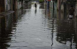 A woman wades across a flooded area