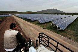 A worker looks on as he rests in a solar farm in Thiva