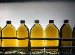 Bottles of whisky pass before light as they are scanned by workers at a bottling house