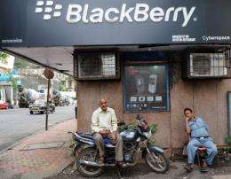 Indian men chat outside a BlackBerry phone store in Mumbai