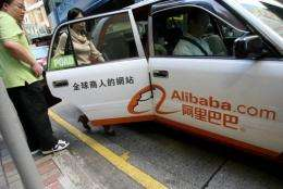 Passengers take a taxi adourned with the logo of e-commerce firm Alibaba in Hong Kong