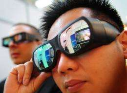 People watch a 3D TV set using special googles at the CeBit 2010 fair in Hanover