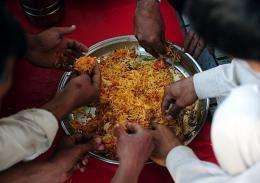 Poverty stricken Pakistani people eat free food outside a charitable organizations office in Karachi