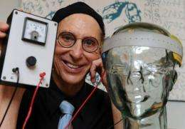 "Professor Allan Snyder displays a ""thinking cap"" (R) on a glass head at the University of Sydney"