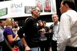 Steve Jobs (C), chief executive officer of Apple Inc., speaks to reporters