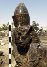 The statue depicts the king sitting on a throne with Amun, the chief deity